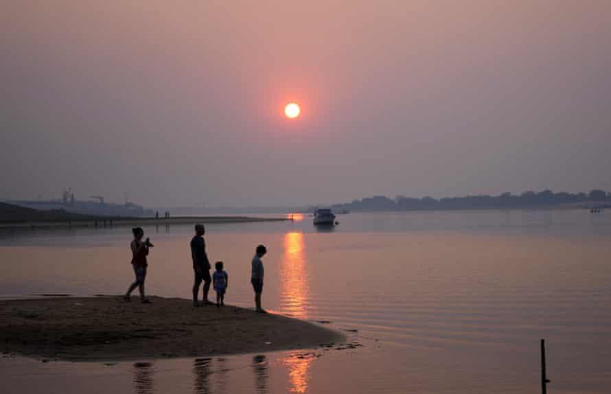 Une famille se tient dans le port, relié au fleuve Paraguay à Asuncion, au Paraguay, en août.
