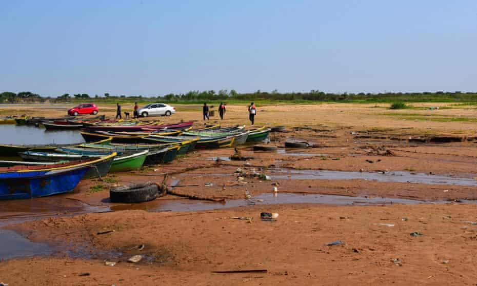 Des gens marchent en barque le long d'un lit exposé d'une branche du fleuve asséché du Paraguay, à Lambare, au Paraguay, le 17 septembre.